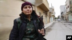 FILE - Kurdish fighter Pervin Kobani rides in the back of a pickup truck through Kobani, Syria. Female fighters have been integral to the war efforts.