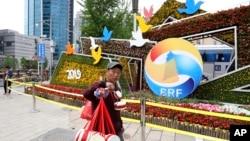 """一名小贩路过宣传4月25日至27日在北京举行的""""一带一路国际合作高峰论坛""""的巨型花卉(2019年4月19日)"""