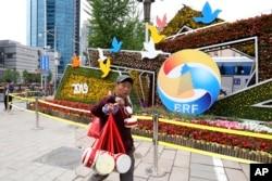 2019年4月19日,北京一带一路峰会论坛的宣传和装饰,一名卖鼓的男子走过。