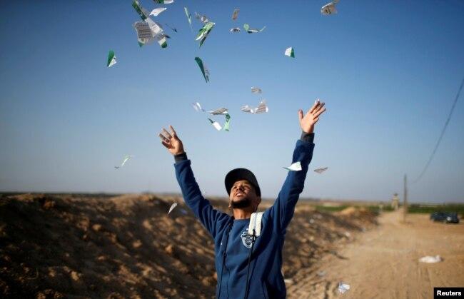 이스라엘 건국일의 다음 날인 '대재앙의 날(nakaba)'을 맞아 가자지구에서 팔레스타인인들의 항의 시위가 계속 되는 가운데, 시위 참가자가 이스라엘군이 살포한 전단지를 하늘에 던지고 있다.