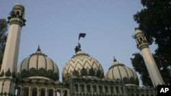 A Muslim man hoists a black flag atop a mosque in Ayodhya, about 600 km (375 miles) southeast of New Delhi, December 6, 2009. Indian Muslims on Sunday observed the 17th anniversary of the razing of the16th century Babri mosque by Hindu mob in the town of