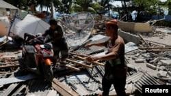5일 인도네시아 휴양지인 롬복에서 6.9 규모의 지진이 발생한 가운데 마을 주민들이 무너진 건물 잔해 사이에서 오토바이를 밀고 있다.