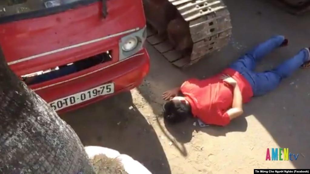 Hình ảnh một người dân nằm xuống trước xe ủi để phản đối việc cưỡng chế đất ở vườn rau Lộc Hưng. Người dân khu vực này đã không được chính quyền cho phép họp báo để công khai thông tin về việc sử dụng đất ở đây.