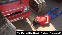 Một người dân nằm chặn xe ủi để phản đối cưỡng chế ở Vườn rau Lộc Hưng.