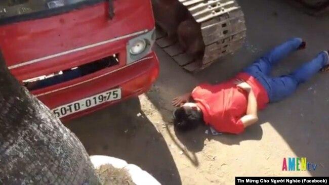 Một người dân dùng thân mình để chặn xe ủi.
