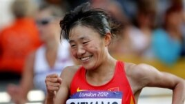 Choeyang Kyi celebrates her third place finish in the women's 20-kilometer race walk at the 2012 Summer Olympics, Saturday, Aug. 11, 2012, in London.  (AP Photo/Emilio Morenatti)