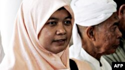 Một nhà hoạt Hồi giáo ở Thái Lan cầm quyển sách có hình luật sự bị mất tích Somchai Neelapaichit trên trang bìa