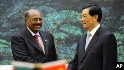 中国国家主席胡锦涛与苏丹总统巴希尔6月29日在北京人民大会堂举行的签字仪式上握手