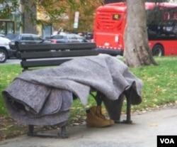 Seorang tunawisma tidur berbalut selimut di bangku taman kota Washington DC. Banyak tunawisma di AS tewas akibat hipotermia pada musim dingin.