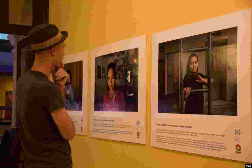"People look at photos of abused domestic workers at an exhibit titled ""No one should work this way"" at the Foreign Correspondents Club of Phnom Penh on May 7, 2015. (Photo: Nov Povleakhena/VOA Khmer)"