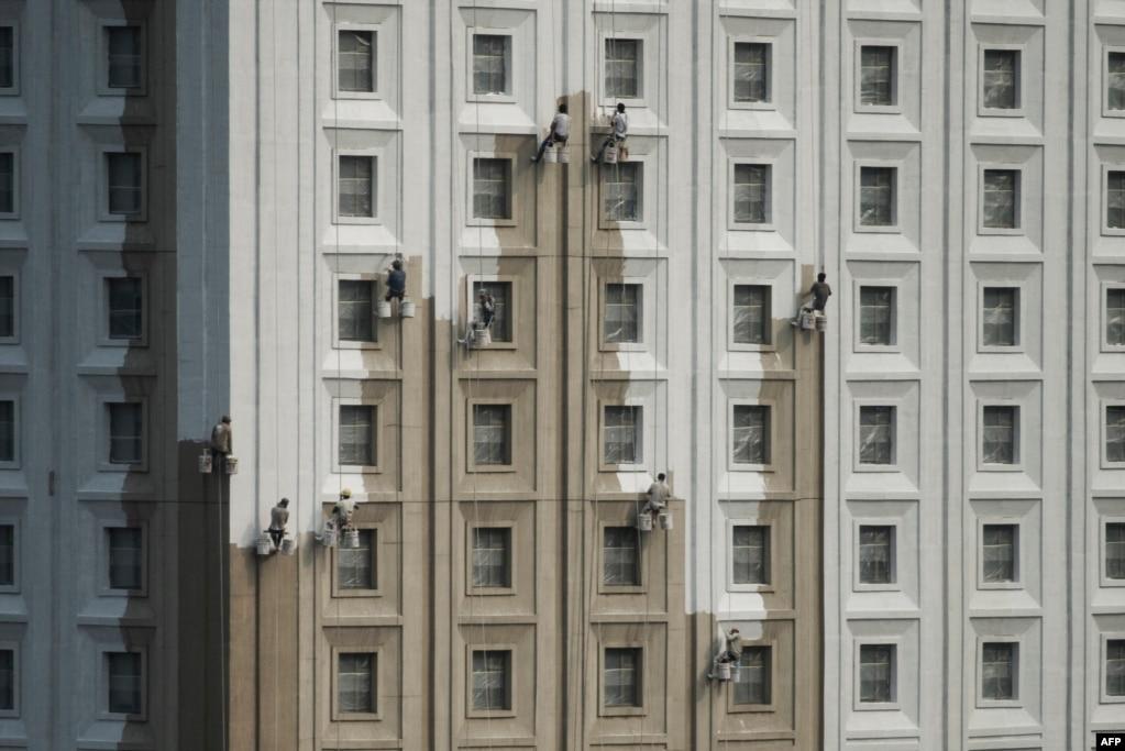 在沈阳的大楼上,工人刷墙(2017年7月13日)。中国国家统计局7月17日公布第二季度中国经济各项指标,其中国内生产总值(GDP)同比增长6.9%,与第一季度持平,好于经济学家预计的6.8%。推动第二季度中国经济增长的行业包括:新建住宅楼,强劲零售额,尤其是线上零售,还有对基础设施的持续大规模投资,如新建高速公路和高铁线路等。外贸的强劲回升也拉动了中国经济第二季度的增长。