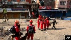 Satu tim SAR dari China bersama anjing pelacak berdiri di dekat sebuah gedung yang rusak akibat gempa di Kathmandu, Nepal, 26 April 2015 (AP Photo / Manish Swarup).