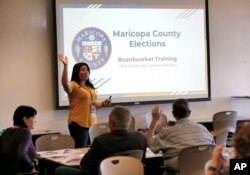 FILE - Maricopa County Elections official Brittney Johnson instructs election volunteers during a training session in Phoenix, Oct. 31, 2018.
