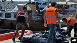 FILE - A Turkish paramilitary officer and local workers collect the bodies of migrants after coast guard officials said 13 migrants died after their boat collided with a ferry off the Turkish coast near Ayvacik, Canakkale, Turkey, Sept. 20, 2015.