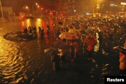 Regu penyelamat dan penduduk setempat berupaya menolong sebuah mobil yang terjebak banjir di Guangqumen, Beijing, (21/7).