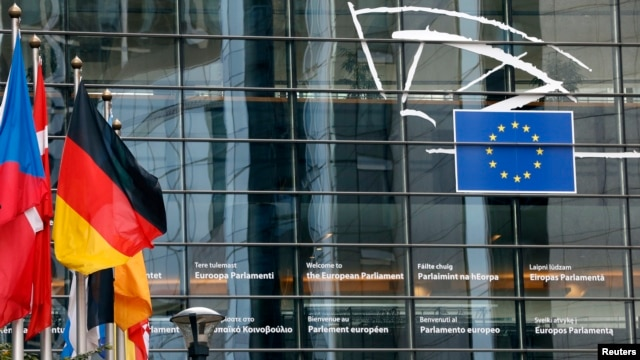 FILE- A German flag flies outside the European Parliament in Brussels, Oct. 21, 2013.