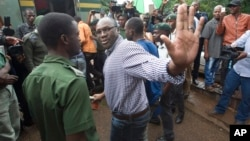 Evans Mawarire salue la foule avant de monter dans un camion prison truck at the magistrates courts in Harare.