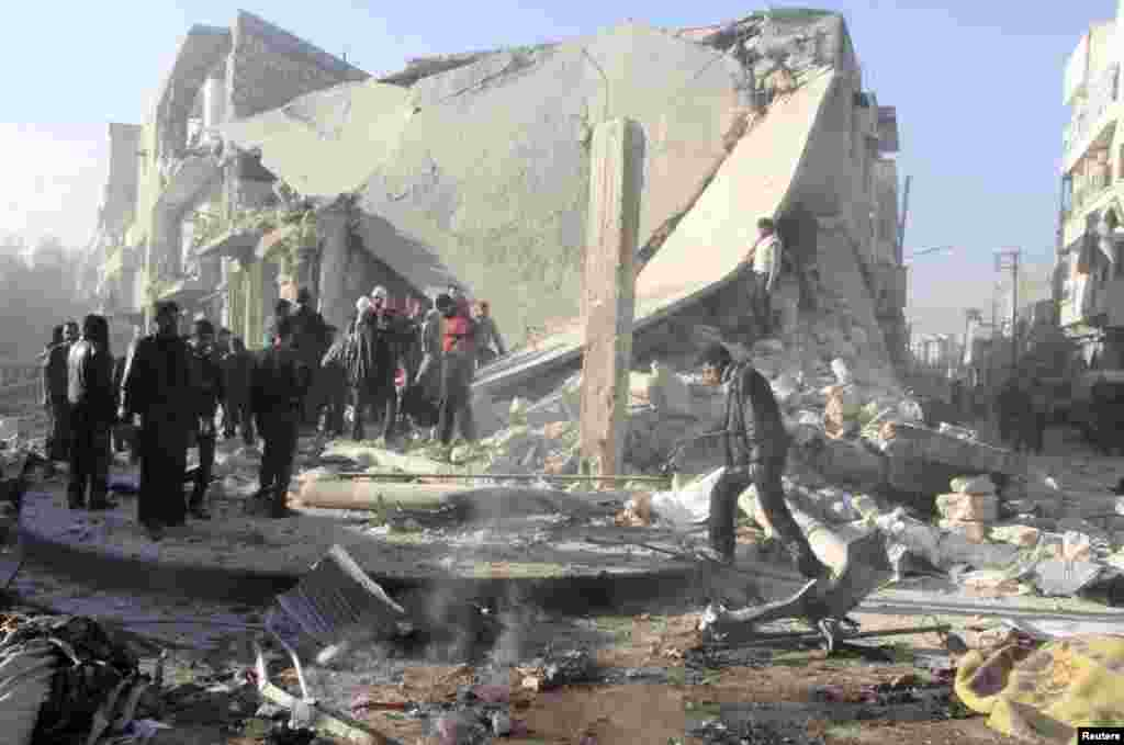People inspect a site damaged by what activists said was an air raid by forces loyal to Syrian President Bashar Al-Assad in the al-Marja district of Aleppo, Dec. 23, 2013.