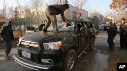 阿富汗一名司機在星期五的爆炸襲擊後清理汽車被震碎的玻璃
