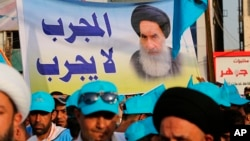 FILE - In this May 4, 2018 photo, followers of Shi'ite cleric Muqtada al-Sadr hold a poster of Shi'ite spiritual leader Grand Ayatollah Ali al-Sistani, during a parliamentary campaign rally in Baghdad.