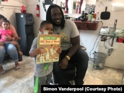 Trey Hopkins, a Cincinnati Bengals football player, reads with Kevelle Boyd at Korporate Kuts Barbershop in Cincinnati, Ohio. Simon Vanderpool started Books, Barbers and Ballers, to bring professional athletes into the reading and mentoring program.