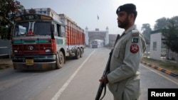 FILE - A paramilitary soldier stands guard as a truck crosses into Pakistan from India at the Wagah border, Nov. 4, 2011.