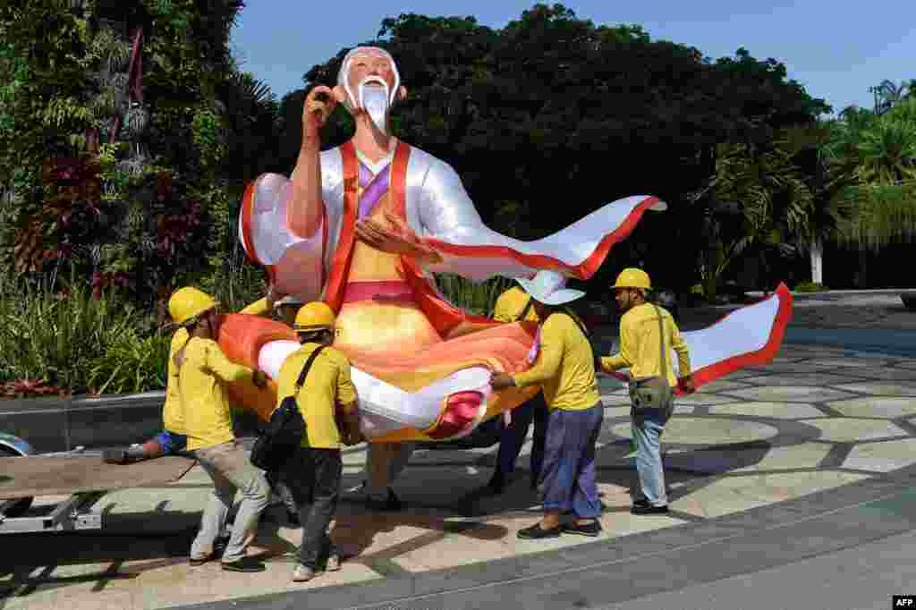 Workers carry a lantern figurine of matchmaker Yue Xia Lao Ren (Old Man under the moon) in preparation for the upcoming Mid-Autumn Festival at Garden by the Bay in Singapore.