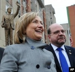 U.S. Secretary of State Hillary Rodham Clinton smiles in front of a statue of her husband former President Bill Clinton, in Pristina, Kosovo, 13 Oct. 2010