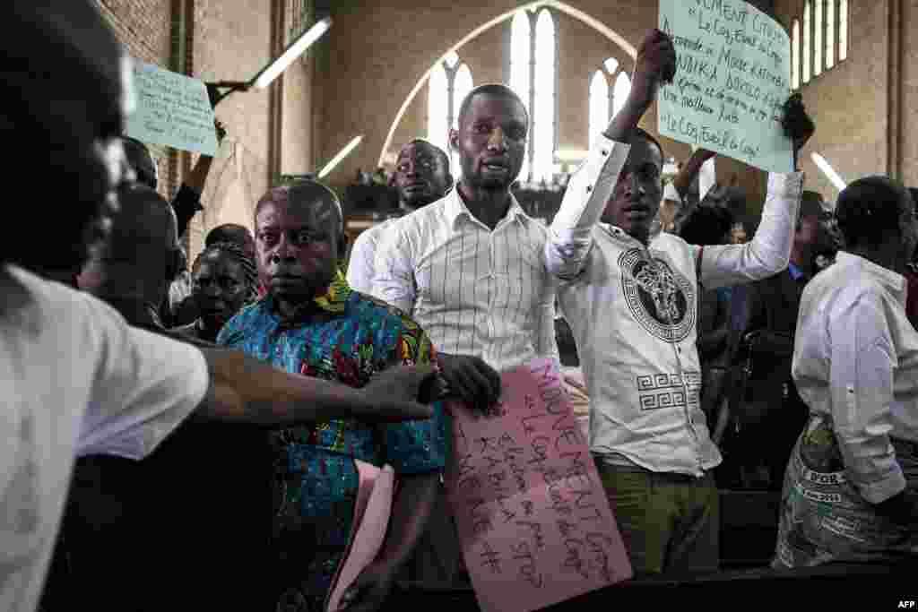 Des manifestants montrent des affiches dans un service catholique pour commémorer les victimes de la répression de la marche du mois dernier, à Kinshasa, le 12 janvier 2018 .
