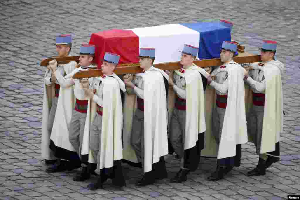 French Foreign Legionnaires carry the coffin of politician Yves Guena during an official funeral ceremony at the Hotel des Invalides in Paris.