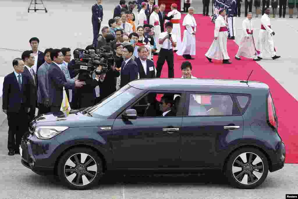 Pope Francis in his popemobile car as South Korean President Park Geun-hye watches upon his arrival at Seoul Air Base in Seongnam, August 14, 2014.