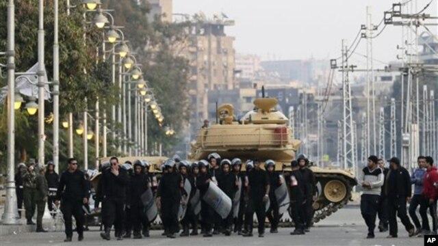 Polisi anti huru-hara Mesir berjaga di sekitar istana kepresidenan di Kairo, Mesir (16/12).  Kelompok oposisi utama Mesir menyatakan penyelenggaraan putaran pertama referendum konstitusi Minggu kemarin dicemari pelanggaran dan menyerukan diadakannya pemungutan suara ulang.