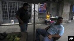 Vendedores ambulantes esperan clientes cerca de un cartel de la campaña de apoyo del presidente de Venezuela, Hugo Chávez, en Caracas, Venezuela.