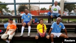 A group of senior soccer players rest after a match in Miraflores, in Lima.