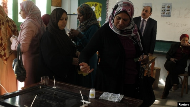 A woman dips her finger in ink after casting her vote in a referendum on Egypt's new constitution, at a school used as a polling station in Alexandria, Egypt, December 15, 2012.