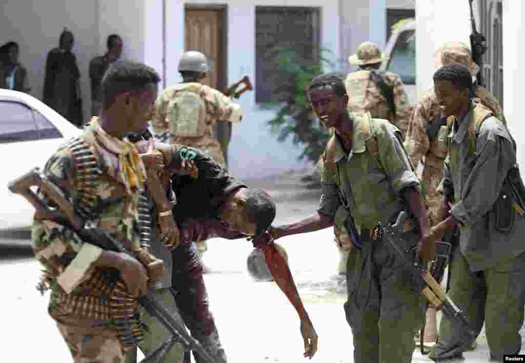 Somali soldiers help a wounded civilian, Mogadishu, April 14, 2013.