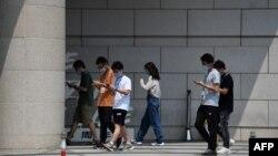 北京一群青年邊走路邊看手機。 (2020年7月6日)