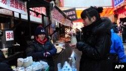 一妇女设摊出售传统北京酸奶