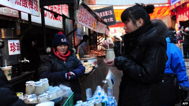 A vendor selling jars of traditional Beiijng yogurt stands at her stall after selling to a customer in Beijing on January 20, 2011.