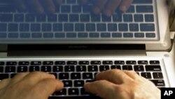 Un homme tape sur le clavier d'un ordinateur, le 27 février 2013.