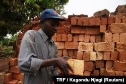 Erastus Njiru carries mud bricks in Kivoo, eastern Kenya, March 3, 2018.