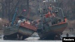 Một tàu chở hàng (phải) trên bờ sông Yalu ở Sinuiju, đối diện với thành phố biên giới của Trung Quốc Đan Đông, ngày 14 tháng 3 năm 2016.