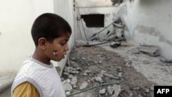 Một bé trai Libya đứng cạnh căn nhà bị hư hỏng sau vụ pháo kích của lực lượng Gadhafi vào thị trấn Misrata, ngày 21/6/2011