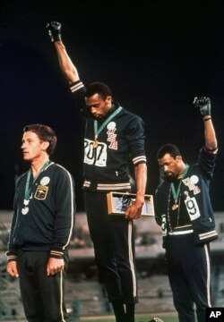 "FILE - U.S. athletes Tommie Smith, center, and John Carlos raise their black-gloved firsts in racial protest during the playing of ""The Star-Spangled Banner"" after Smith received the gold and Carlos the bronze medal in the 200-meter run at the Summer Olympic Games in Mexico City, Oct. 16, 1968."