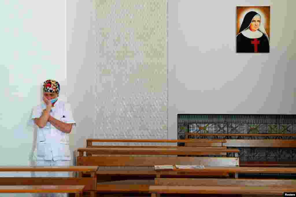 A medical staff member is seen inside the chapel in the San Giovanni hospital before the chaplains bring a cross outside to give a blessing to the medical staff on Good Friday, as Italy is under lockdown to try to stop the spread of the coronavirus diseas