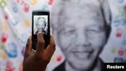 一位祝愿曼德拉康复的人7月18日在曼德拉入住的比勒陀利亚亚医院外用手机拍照一个横幅上的曼德拉肖像
