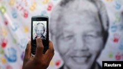 A well-wisher takes a picture of a banner with the image of former South African president Nelson Mandela, outside the hospital where he is being treated, in Pretoria July 18, 2013.