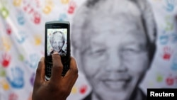 A well-wisher takes a picture of a banner with the image of former South African President Nelson Mandela, outside the hospital where he is being treated, in Pretoria, July 18, 2013.