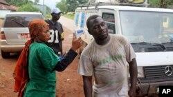 畿內亞衛生工作者給人量體溫。(2014年9月7日)