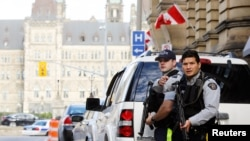 FILE - Armed RCMP officers guard access to Parliament Hilll following a shooting incident in Ottawa. Canada's national police force say they have thwarted what they believe was a suicide bomb plot.